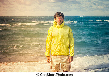 Man Traveler on beach seaside with sea waves on background summer vacations Lifestyle concept