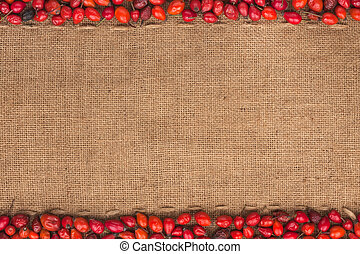 Rosehip lying on sackcloth, with space for text