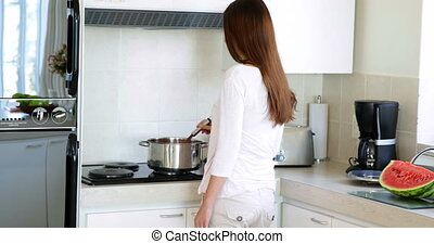 Pretty woman preparing dinner at the stove at home in the...