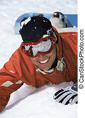 Young snowboarder lying in the snow