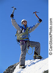 Young man celebrating on snowy peak