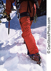 Close-up of young man mountain climbing on snowy peak
