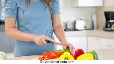 Smiling woman preparing vegetables on the chopping board at...