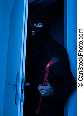 Thief Holding Crowbar While Entering Into House - Thief...