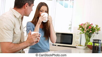 Happy couple drinking coffee together at home in the kitchen