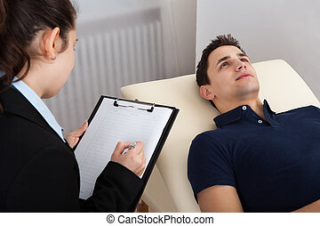 Patient Lying On Bed While Psychologist Writing Notes