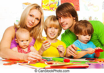 Family and craft - Young family with three kids sitting by...