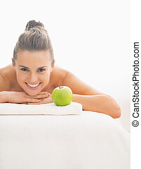 Smiling young woman with apple laying on massage table