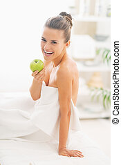 Smiling young woman sitting with apple on massage table
