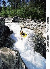 Young man kayaking in rapids