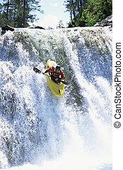 Young man kayaking down waterfall