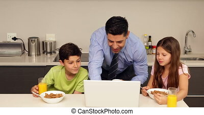 Smiling father using laptop with children before he goes to...