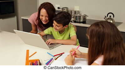 Mother using laptop with son while daughter is drawing at...