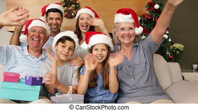 Happy extended family waving at camera at christmas time at...