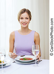 smiling young woman eating appetizer at restaurant -...
