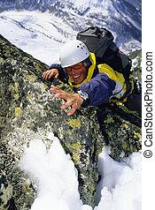 Mountaineer climbing snowy rock face