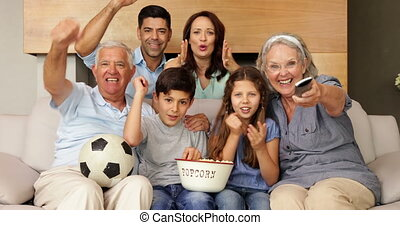 Happy extended family watching football on tv at home in the...