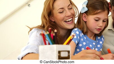 Happy parents and daughter colouring together at home in...