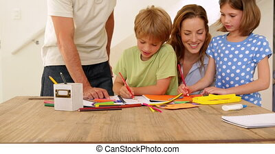 Happy parents and children drawing together at the table at...