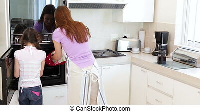 Mother and daughter taking hot cookies from oven - Mother...