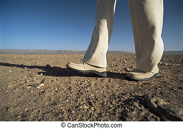 Man walking in desert, low section, ,