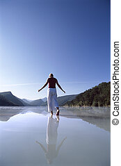 Young woman wading in lake