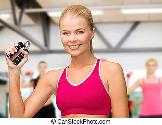 smiling woman with hand expander - fitness, healthcare and...