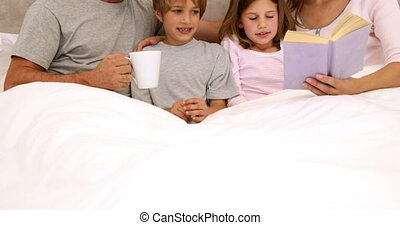 Smiling parents and children reading together in bed at home...