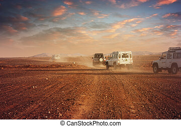 Cars in the desert at sunset