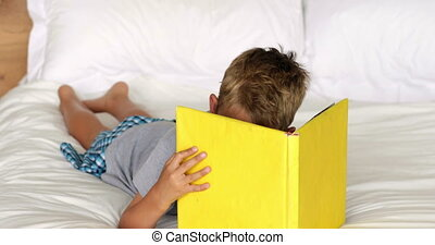 Little boy reading yellow book on bed - Little boy reading...