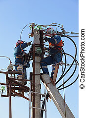 Electricians working at height on a support with linear...