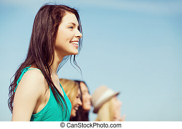 girl with friends walking on the beach - summer holidays and...