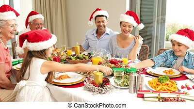 Siblings pulling a christmas cracker at the dinner table at...