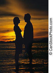 Silhouette of couple standing face to face on beach at...