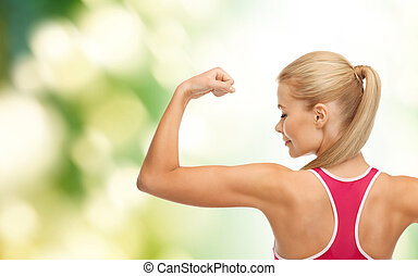 sporty woman showing her biceps - fitness and healtcare...