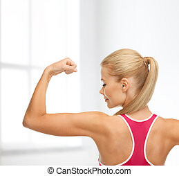 sporty woman showing her biceps - fitness and home concept -...