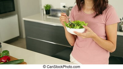 Pretty woman eating a bowl of salad