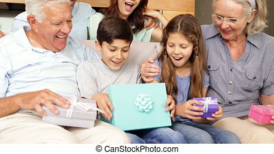 Happy extended family opening gifts on the couch at home in...