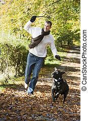 Man exercising dog in woodland