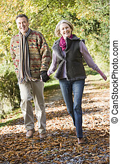 Senior couple walking through autumn woods - Senior couple...