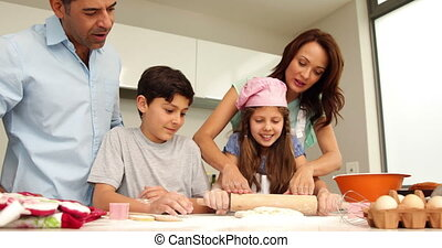 Mother helping daughter to roll out dough with her family at...