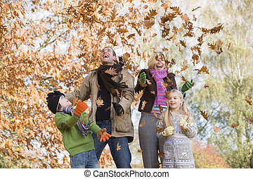 Family throwing leaves in the air - Father throwing autumn...