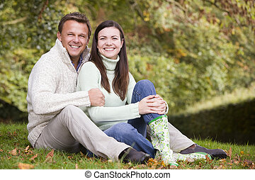 Couple sitting in autumn woods