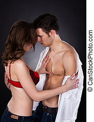 Lusty Woman In Bra Removing Man's Shirt - Young lusty woman...