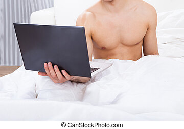 Midsection Of Shirtless Man Holding Laptop In Bed -...