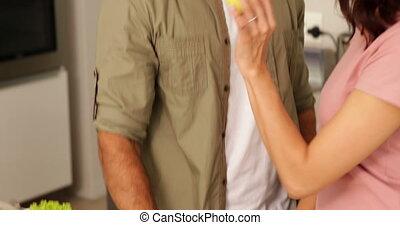 Woman feeding her boyfriend a green apple