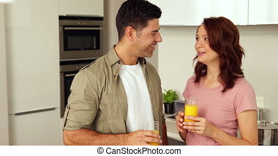 Young couple chatting and drinking orange juice at home in...