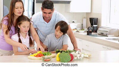 Mother showing her children how to slice vegetables at home...