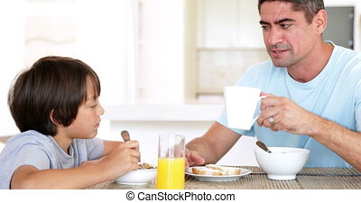 Man chatting with his son over breakfast at home in the...