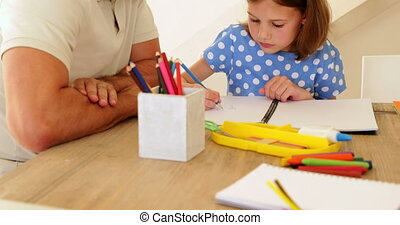 Father and daughter drawing together at the table at home in...